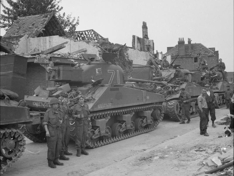 THE BRITISH ARMY IN THE UNITED KINGDOM 1939-45 (H 38995) A Sherman Firefly and Sherman tanks of 'C' Squadron, 13th/18th Royal Hussars waiting to be loaded aboard landing ships at Gosport, 3 June 1944. The Firefly crew in the left foreground are Trooper Fred Shaw, Trooper Doug Kay, Sergeant Fred Scamp and Trooper Bill Humphries. Their vehicle was named 'Carole'. Copyright: © IWM. Original Source: http://www.iwm.org.uk/collections/item/object/205126259